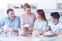 Loving family reuniting during delicious meal time. Family time is wisely spent time. Thoughtful mother smiling while taking care of her family members and Stock Photo
