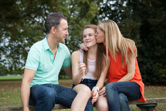 Loving Family. Sitting in a park having a good time, laughing and goofing around stock image