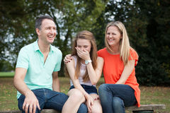 Loving Family. Sitting in a park having a good time, laughing and goofing around stock photos