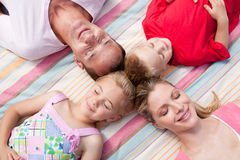 Loving family sleeping lying on the grass. In a park Royalty Free Stock Photography