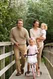 Loving family on small bridge in the park. Portrait of loving young family of four on small bridge in the park royalty free stock photography