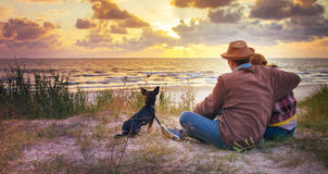 Loving family at sunset sea. Loving couple and their dog watching beautiful sunset near the sea royalty free stock photo