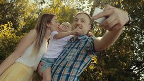 Loving family taking photo in green forest. Mother kisses little son stock video footage