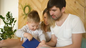 Loving family of three lying on bed in morning. Family hugging and reading book stock video