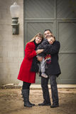 Loving Family Warmly Dressed Hugging Son in Front of Rustic Building Stock Photo