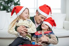 Loving Father With Arms Around Children. Sitting on floor during Christmas at home Royalty Free Stock Photo
