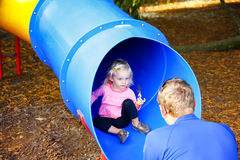 Loving father catching his little daughter at the slide. Royalty Free Stock Images