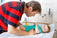Loving father changing diaper of his newborn baby daughter. Little child, girl on changing table in bathroom with rattle toys. Happy dad Royalty Free Stock Photos