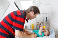 Loving father changing diaper of his newborn baby daughter. stock images