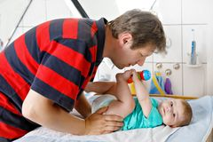 Loving father changing diaper of his newborn baby daughter. Stock Image