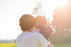 Loving father cradling his young baby in his arms. Loving protective father cradling his young baby in his arms in the warm glow of the sunlight stock photos