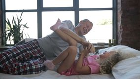 Loving father and cute daughter playing in bed stock video footage