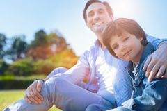 Loving father embracing his son outdoors. Harmonious relations. Selective focus on a charming youngster looking into the camera with a slight smile on his face Royalty Free Stock Photo