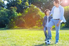 Loving father embracing son after playing football. So proud of him. Thoughtful mature men smiling to his son while their legs standing on a soccer ball after an Stock Images