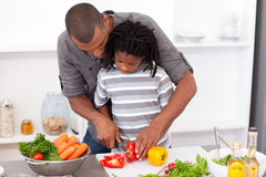 Loving father helping his son cut vegetables stock image
