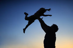 Loving father and his little son having fan together outdoors. Family as silhouette on sunset. Royalty Free Stock Photo