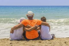 Loving father with his son and daughter in obhimku rest on the seashore or the ocean.  royalty free stock image
