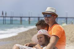 Loving father with his son and daughter in obhimku rest on the seashore or the ocean.  stock photo