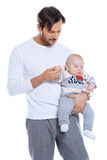 Loving father holding his small baby. Loving father standing holding his small baby on his arm studio portrait isolated on white Stock Photography