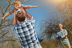 Loving father holding his son in hands. Have some fun,. Caring nice men holding his smiling son in hands and spinning him while cheerful grandfather standing in Stock Photo