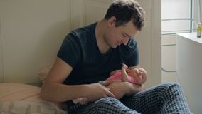 Loving father holding newborn daughter and kissing her stock video
