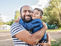 A loving father holds a child in his arms. Emotional photo. royalty free stock photos
