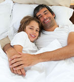 Loving father hugging his son lying on the bed stock photos