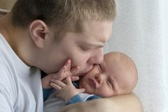 Loving father hugs and kisses his newborn son, close-up. A loving father hugs and kisses his newborn son, close-up stock image