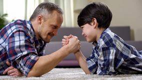 Loving father and kid arm wrestling on the floor, weekend leisure at home, fun. Stock photo royalty free stock photography