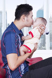 Loving father kissing baby in apartment Royalty Free Stock Image