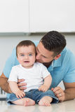 Loving father kissing baby sitting on counter royalty free stock photography