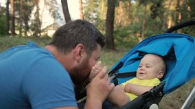 Loving father kissing feet of his baby son in park stock footage