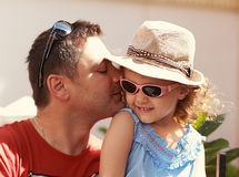 Loving father kissing his happy child girl in sun glasses. On nature summer background Royalty Free Stock Images