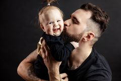 Father kissing adorable baby. Loving father kissing his little baby daughter holding her on hands at studio black background with copyspace. Strength, Power Royalty Free Stock Images