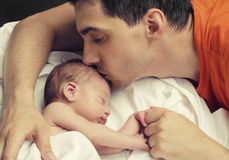 Loving father kissing his new born baby. Father kissing his baby boy forehead while his sleeping and holding hands. Parent love Royalty Free Stock Photography