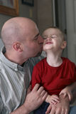Loving Father Kissing Son. Father is holding his toddler aged son and the father is kissing his son on the cheek. The toddler is smiling Stock Photography