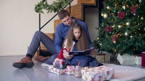 Joyful family reading fairy tale at christmas time stock footage