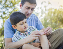 Loving Father Puts Bandage on Knee of Young Son Royalty Free Stock Photo
