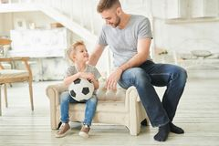 Loving Father Talking to Cute Son. Full length warm toned  portrait of caring father talking to cute little son holding football ball sitting on small couch at royalty free stock images