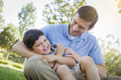 Loving Father Tickling Son in the Park Stock Images