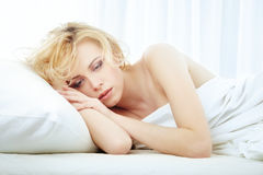 Loving and feeling sad. Sad enamored lady laying in the bedroom Royalty Free Stock Images