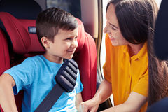 Loving female checking son sitting in baby seat Royalty Free Stock Photo