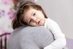Loving Girl Hugging Mom At Home. Closeup of female child leaning on mother`s shoulder at home stock images