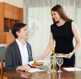 Loving girl serving dinner to beloved man Stock Image