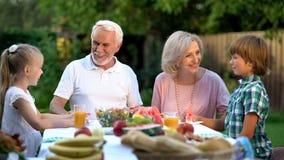 Loving grandchildren visiting grandparents, happy senior couple admiring kids stock photo