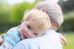 Loving grandfather holding his little grandchild Stock Photos