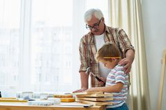 Loving Grandfather and Little Boy Making Wooden Models Together Royalty Free Stock Photo