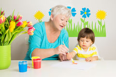 Loving grandma teaching grandson drawing at home. Loving grandma teaching her grandson to draw with paint at home Royalty Free Stock Photo