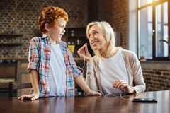 Loving grandmother asking her grandchild for listening to music together Stock Photography