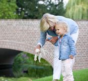 Loving grandmother standing outdoors with little girl Stock Photo